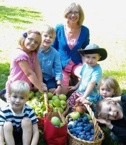 Kindergarten class in Beaverton, Oregon happily harvesting fruit with their teacher.