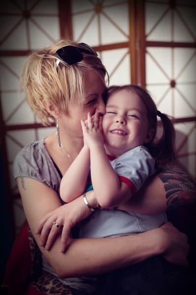 Mother kissing her preschool daughter at Living Wisdom School in Beaverton, Oregon